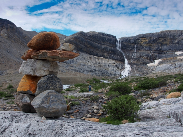 A little inukshuk points to Bow Glacier Falls