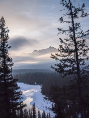 East end of Rundle barely visible through the clouds, with the partially frozen Bow River below