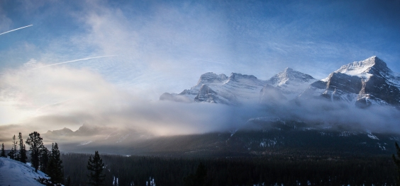 Contrails arc the sky over Mount Rundle