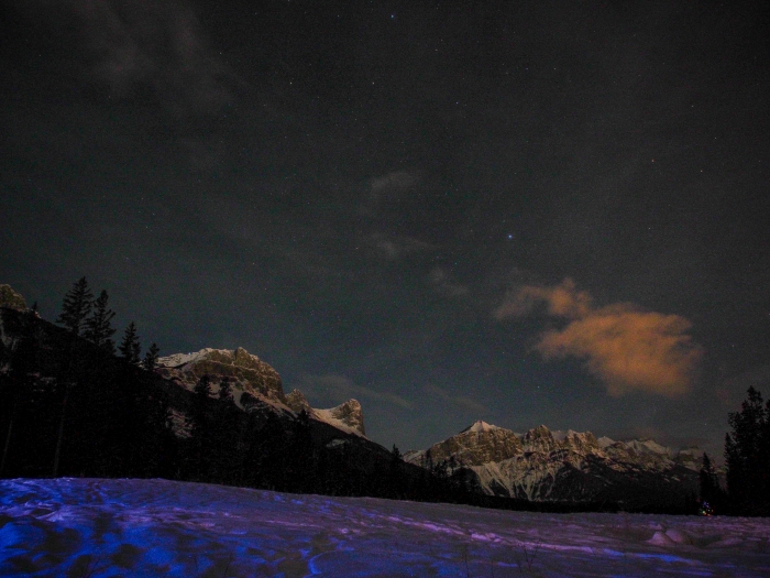 Taken from a snow-covered fairway on the unfinished Three Sisters golf course, from left to right are snow-capped Miner's Peak, Ha Ling and Mount Rundle under a starry sky.