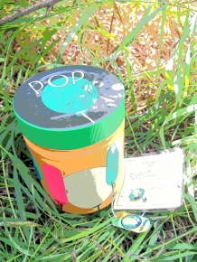 Colourful geocache container and travel bug