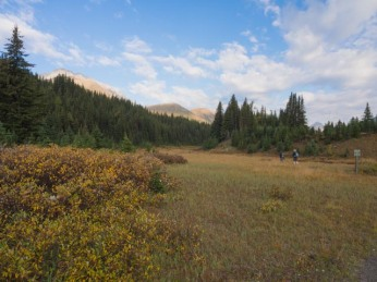 K and Mrs. GeoK cross Highwood Meadow. Pocaterra Ridge is the double-peaked hill just left of the bunch of conifers.