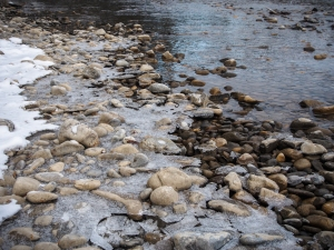 As the water in the Bow River continues to recede, new areas of rock and silt are exposed and thin layers of crunchy ice form along the banks.
