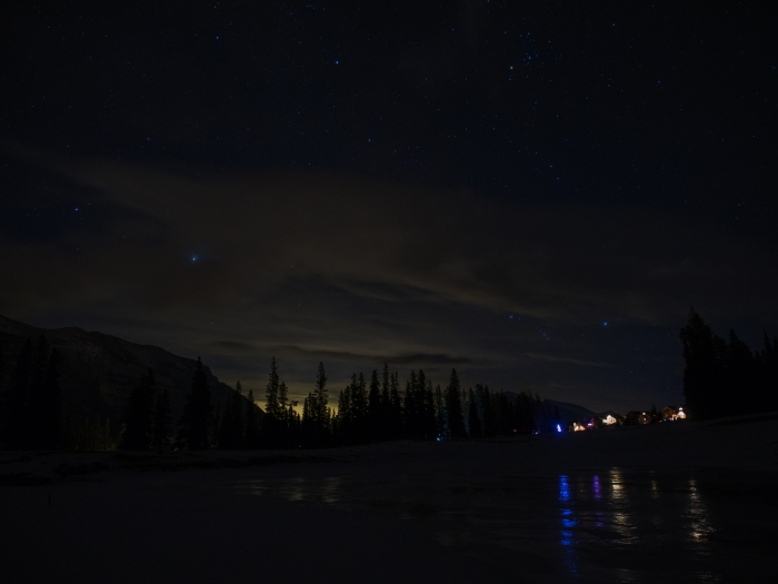 Christmas lights reflecting off snow and ice offer a positive take on artificial light, while the light pollution from somewhere (the LaFarge plant, Dead Man's Flats or even Calgary?) reflecting off the clouds makes a compelling case in support of dark sky preserves.  ~ photo by Mr. GeoK