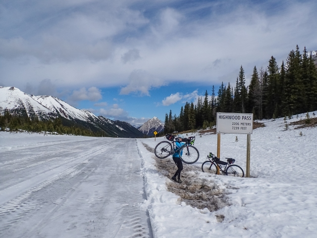 woman-carries-bike-highwood-pass